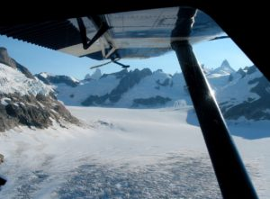 Flying over an ice field with notorious Devils Thumb peak in the background.