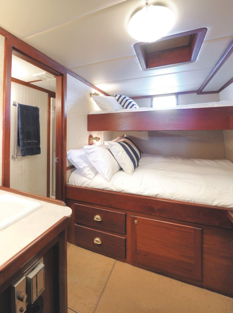 Guest cabin with lower double bed and upper single berth.